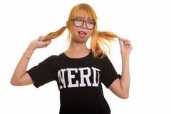 Giovane donna asiatica felice del nerd che sorride e che gioca con i suoi capelli w immagine stock
