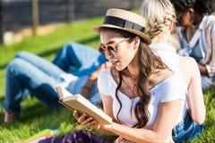 Giovane donna asiatica in libro di lettura del cappello di paglia e degli occhiali da sole mentre sedendosi sull'erba con i compa Fotografia Stock