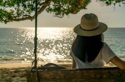 Giovane donna asiatica sedersi e rilassarsi sulle oscillazioni alla spiaggia sulle vacanze estive Vibrazioni di estate Viaggio de fotografia stock libera da diritti