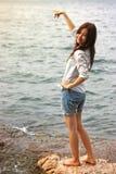 Giovane donna asiatica sorridente che indica su ed esaminare la macchina fotografica fotografie stock
