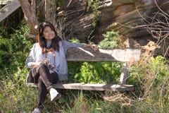 Giovane donna asiatica sudorientale su un banco in primavera fotografie stock