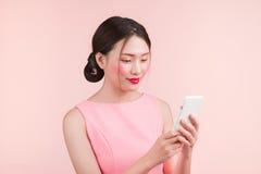 Giovane donna asiatica sveglia con lo smartphone della tenuta di trucco di modo fotografia stock