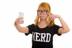 Giovane donna asiatica sveglia del nerd che prende selfie con il telefono cellulare e fotografie stock libere da diritti