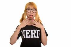 Giovane donna asiatica sveglia del nerd che sembra colpita fotografia stock