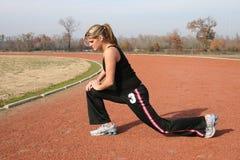 Giovane donna atletica che allunga alla pista Immagini Stock