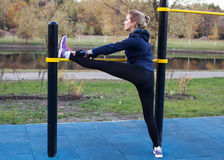 Giovane donna atletica che allunga la gamba Fotografie Stock Libere da Diritti