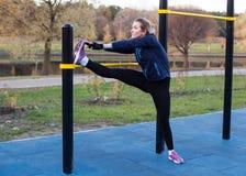 Giovane donna atletica che allunga la gamba Immagini Stock