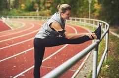 Giovane donna atletica che allunga sullo stadio Fotografia Stock Libera da Diritti