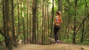 Giovane donna atletica che corre giù Forest Trail And Going Down dalla collina archivi video