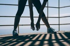 Giovane donna atletica che fa allungamento di mattina sulla parte posteriore Immagini Stock