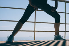 Giovane donna atletica che fa allungando le gambe di mattina sul Fotografia Stock