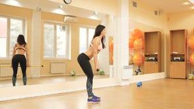 Giovane donna atletica che fa gli esercizi con il bastone acrobatico in palestra video d archivio