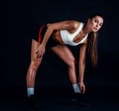 Giovane donna atletica che fa un allenamento di forma fisica contro il fondo nero Donna sportiva in abiti sportivi con l'ente per Fotografie Stock