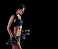 Giovane donna atletica che fa un allenamento di forma fisica contro il fondo nero La ragazza attraente di forma fisica che pompa  Fotografia Stock Libera da Diritti