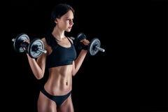 Giovane donna atletica che fa un allenamento di forma fisica contro il fondo nero La ragazza attraente di forma fisica che pompa  Fotografie Stock Libere da Diritti