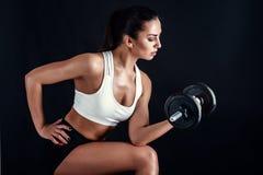 Giovane donna atletica che fa un allenamento di forma fisica contro il fondo nero La ragazza attraente di forma fisica che pompa  Fotografia Stock