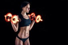 Giovane donna atletica che fa un allenamento di forma fisica contro il fondo nero La ragazza attraente di forma fisica che pompa  Immagine Stock Libera da Diritti