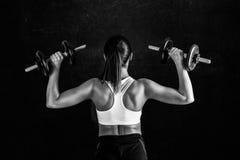 Giovane donna atletica che fa un allenamento di forma fisica contro il fondo nero La ragazza attraente di forma fisica che pompa  Fotografie Stock