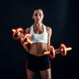 Giovane donna atletica che fa un allenamento di forma fisica contro il fondo nero La ragazza attraente di forma fisica che pompa  Immagini Stock