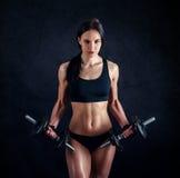Giovane donna atletica che fa un allenamento di forma fisica contro il fondo nero La ragazza attraente di forma fisica che pompa  Immagine Stock