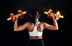 Giovane donna atletica che fa un allenamento di forma fisica contro il fondo nero La ragazza attraente di forma fisica che pompa  Immagini Stock Libere da Diritti