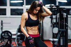 Giovane donna atletica che mostra i muscoli dopo l'allenamento nella palestra fotografie stock