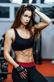 Giovane donna atletica che mostra i muscoli dopo l'allenamento nella palestra fotografia stock libera da diritti
