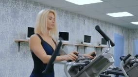 Giovane donna atletica che risolve sulla macchina passo passo alla palestra video d archivio