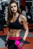 Giovane donna atletica dopo l'allenamento duro alla palestra La ragazza di forma fisica tiene l'agitatore con nutrizione allegra Fotografia Stock