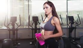 Giovane donna atletica dopo l'allenamento duro alla palestra La ragazza di forma fisica tiene l'agitatore con nutrizione allegra Immagine Stock Libera da Diritti