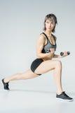 Giovane donna atletica nell'addestramento degli abiti sportivi con le teste di legno Fotografia Stock Libera da Diritti