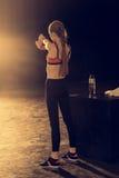 Giovane donna atletica nell'allungamento degli abiti sportivi Immagine Stock