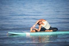 Giovane donna atletica nella posa della curvatura del lato di pratica di yoga del SUP in ala Fotografia Stock