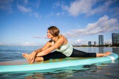 Giovane donna atletica nella posa della curvatura del lato di pratica di yoga del SUP in ala Immagine Stock