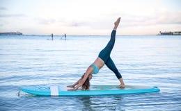 Giovane donna atletica nella posizione dell'ascensore della gamba della curvatura del lato di pratica di yoga del SUP Immagini Stock
