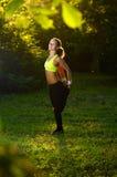 Giovane donna atletica in vestito da sport che fa allungamento di forma fisica Fotografia Stock Libera da Diritti
