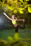 Giovane donna atletica in vestito da sport che fa allungamento di forma fisica Immagine Stock Libera da Diritti
