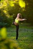 Giovane donna atletica in vestito da sport che fa allungamento di forma fisica Fotografie Stock