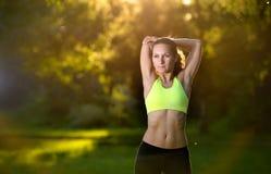 Giovane donna atletica in vestito da sport che fa allungamento di forma fisica Fotografia Stock