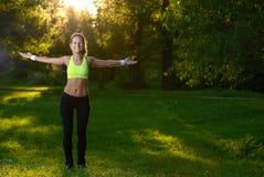 Giovane donna atletica in vestito da sport che fa allungamento di forma fisica Immagini Stock
