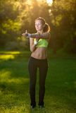 Giovane donna atletica in vestito da sport che fa allungamento di forma fisica Fotografie Stock Libere da Diritti