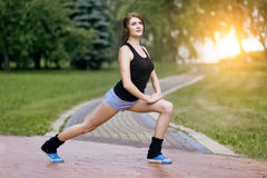 Giovane donna attiva che si scalda nel parco prima di un allenamento fotografia stock