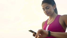 Giovane donna attiva seria che controlla le miglia sul suo orologio corrente fotografia stock