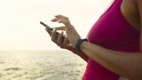 Giovane donna attiva seria che controlla le miglia sul suo orologio corrente fotografie stock