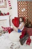 Giovane donna attraente in abbigliamento casuale che si siede sul pavimento N Fotografia Stock