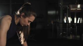Giovane donna attraente in abiti sportivi che fanno spinta-UPS in una palestra di forma fisica La ragazza fa il carico sulle mani archivi video