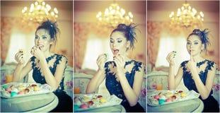 Giovane donna attraente alla moda in vestito nero che mangia i maccheroni in ristorante Bei biscotti castana della tenuta Fotografie Stock