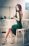 Giovane donna attraente alla moda in vestito verde che si siede nel ristorante Bella testarossa nel paesaggio elegante con una ta