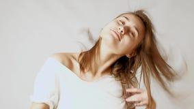 Giovane donna attraente allegra che balla e che gioca con i capelli davanti alla macchina fotografica stock footage