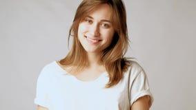 Giovane donna attraente allegra che posa, flirtando, sorridere, giocante con i capelli video d archivio